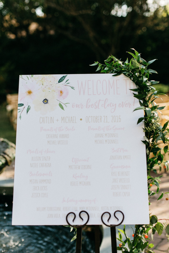 wedding program sign with floral garland