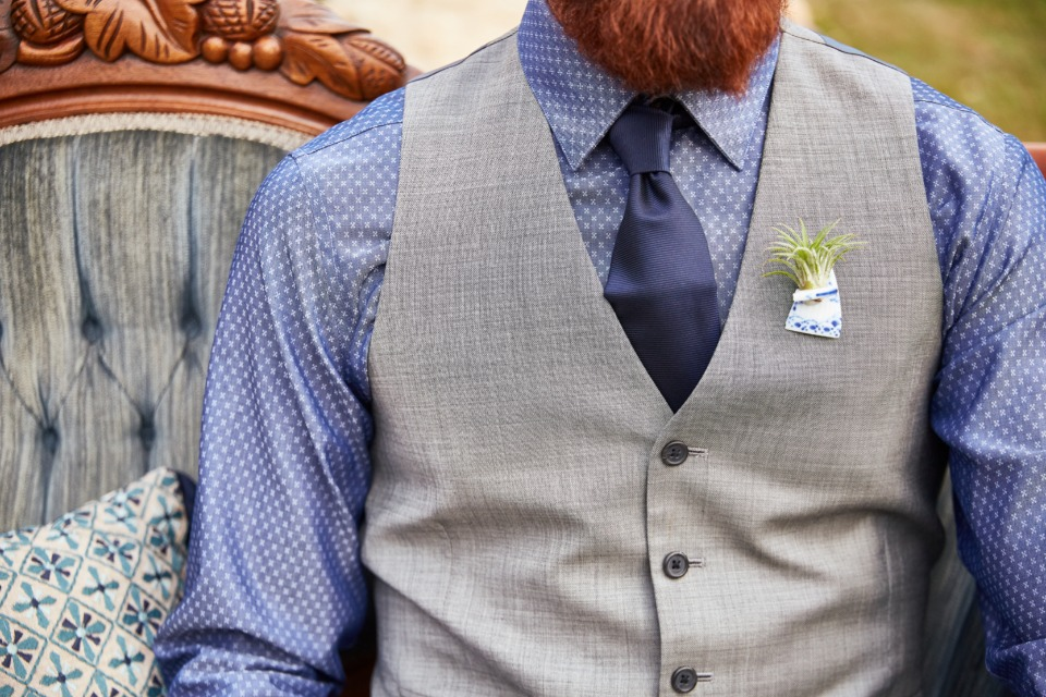 blue and grey groom look with unique hair plant boutonniere