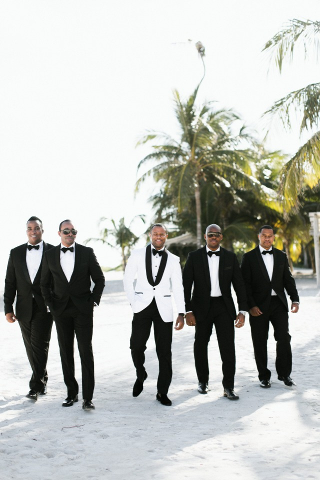 groomsmen in black and groom in white jacket