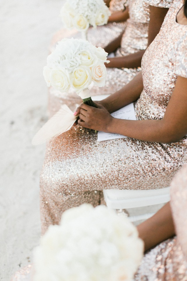 bridesmaids in rose gold sequin dresses with white bouquets
