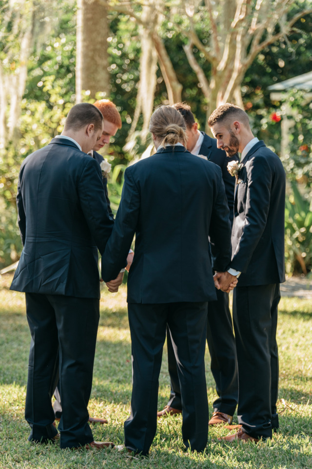 groomsmen prayer circle before wedding