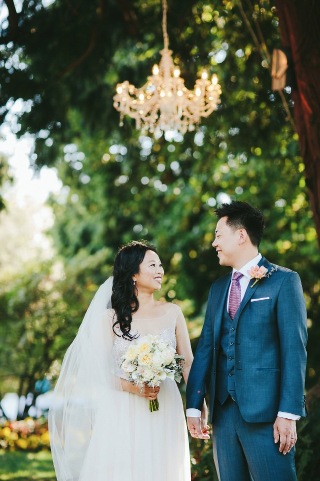 bride and groom under a chandelier