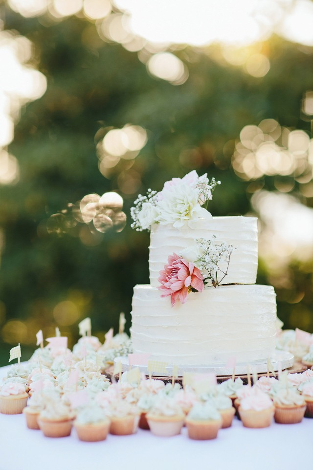 flower topped wedding cake with mini cupcakes