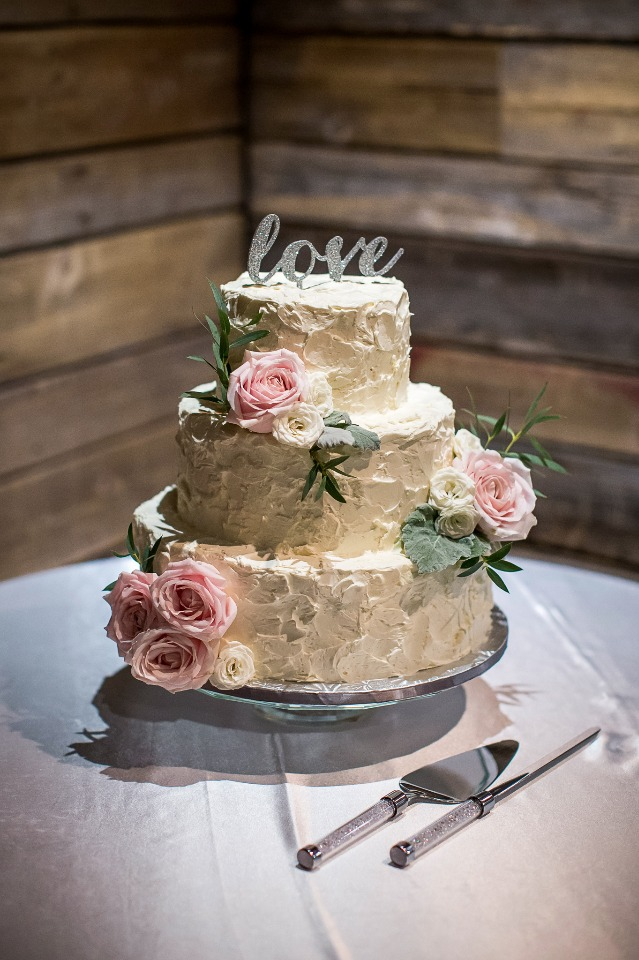 """White cake with flowers and """"love"""" cake topper"""