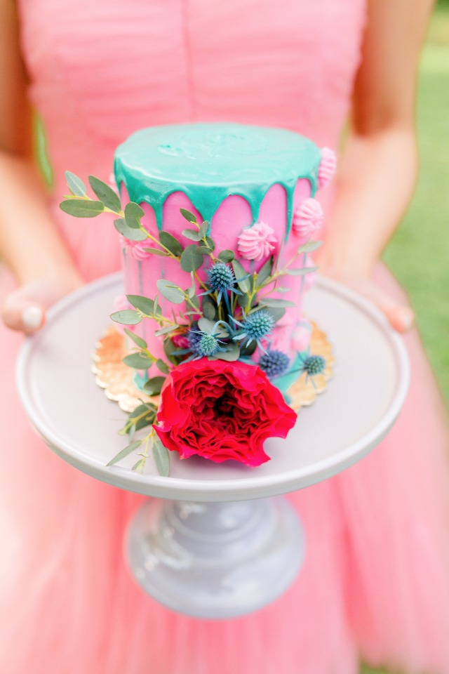 hot pink and teal drizzle cake with floral accents
