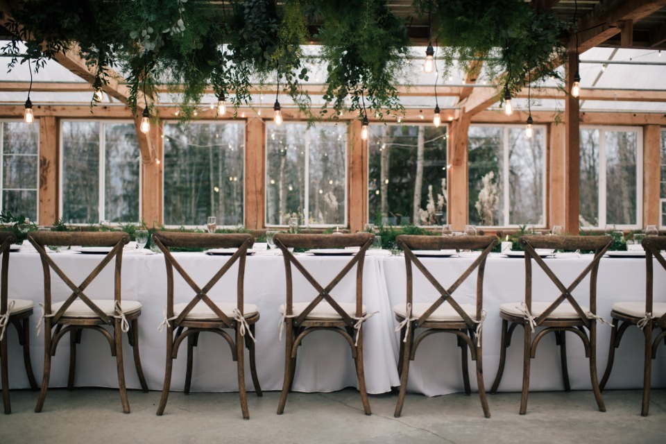 family style seating with modern lighting and greenery table halo