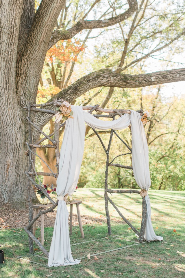 Rustic wood arbor with draped fabric