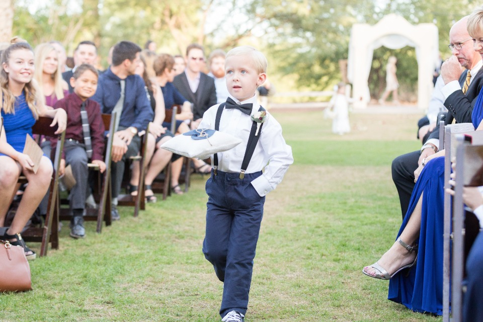 ring bearer in suspenders and bow tie