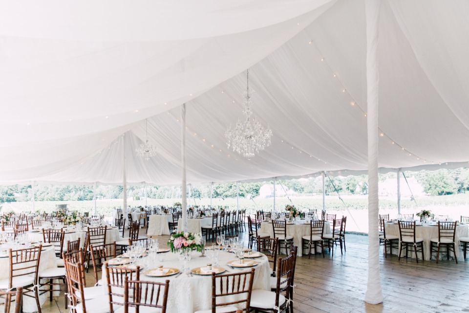 Gorgeous tent reception with chandeliers and bistro lights
