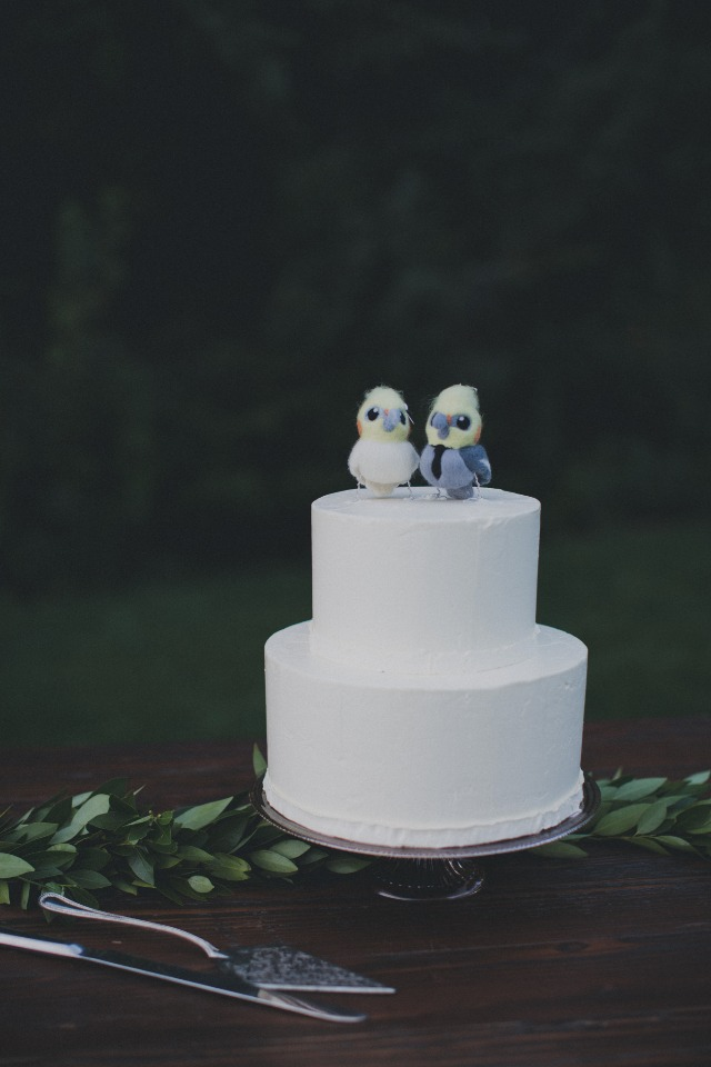 simple white wedding cake and cute bird cake topper