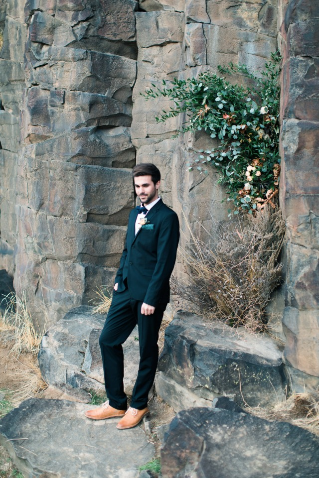 groom in dark suit with bow tie and brown leather shoes