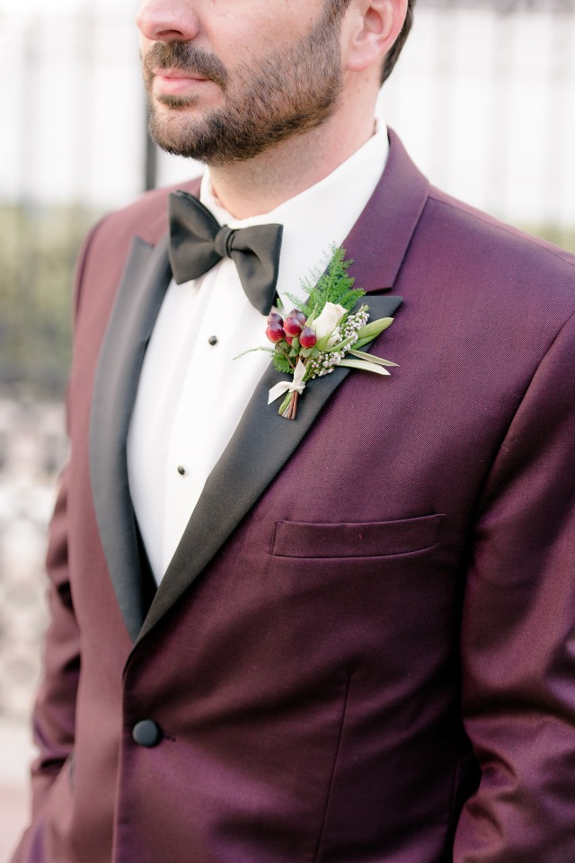 chic groom with green red and white boutonniere