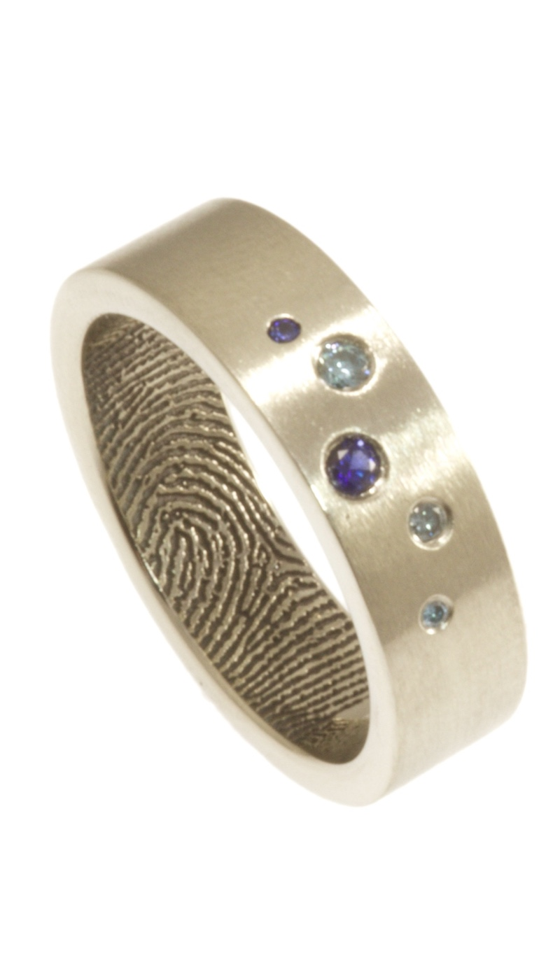 A little bit of blue sparkle with the intimacy of a fingerprint on the interior of the band. Sterling silver, 6mm wide, with 3 blue