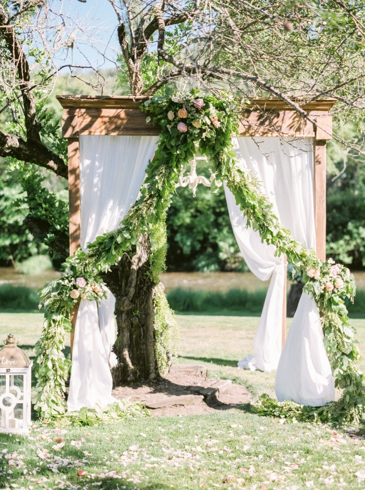 Gorgeous wedding arbor with draped fabric and a chandelier