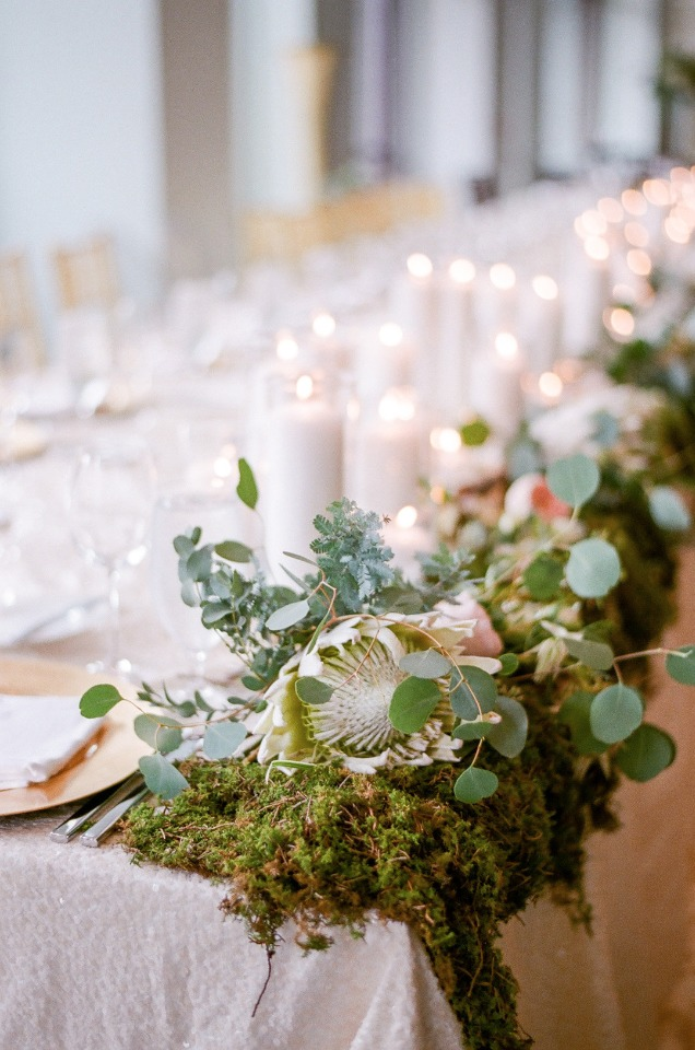 moss protea and candle lit wedding party table