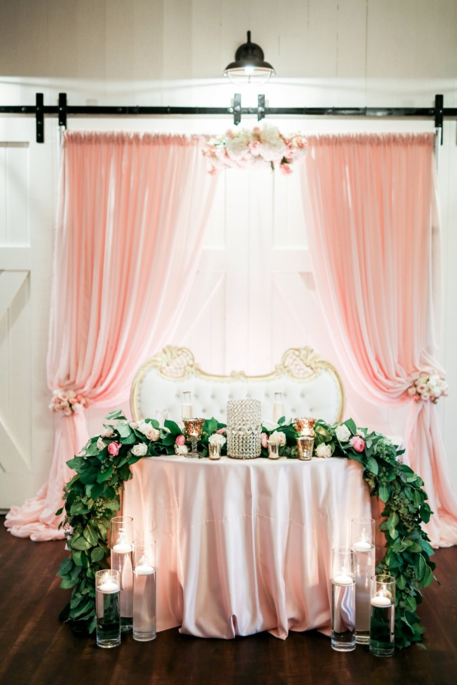Blush and gold sweetheart table with garland