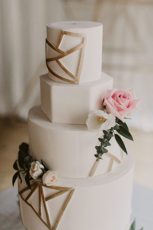 gold and white wedding cake with geometric design