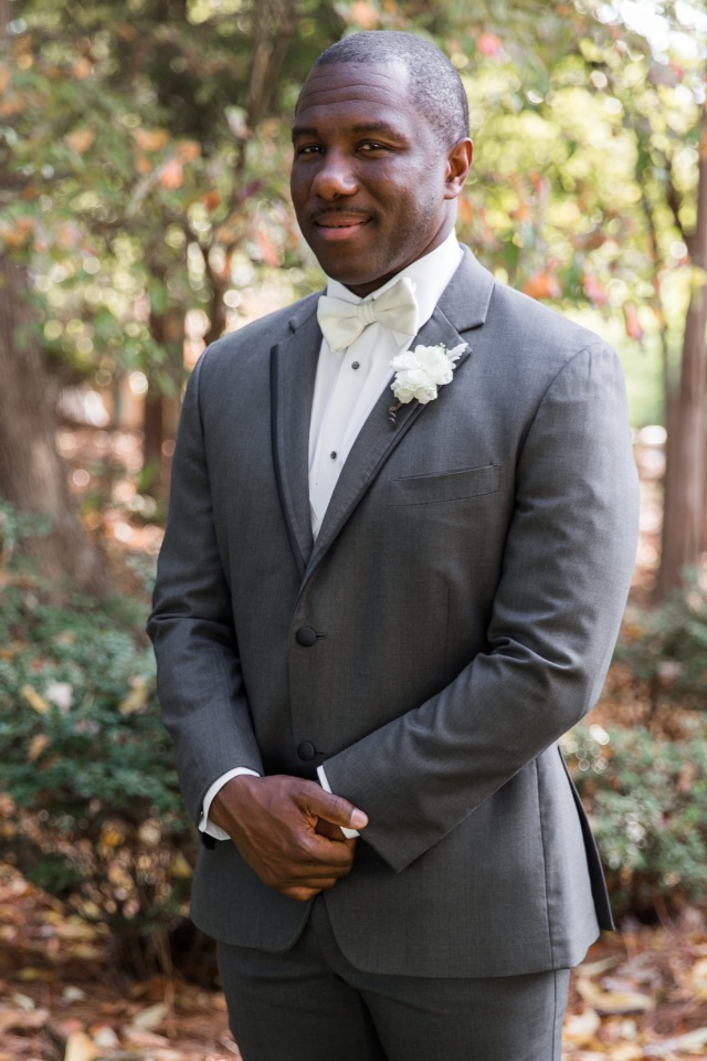 groom in grey suit and white tie
