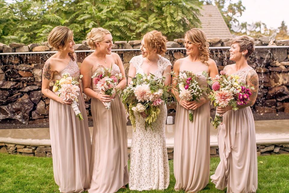 bride and her bridesmaids in long mismatched champagne dresses