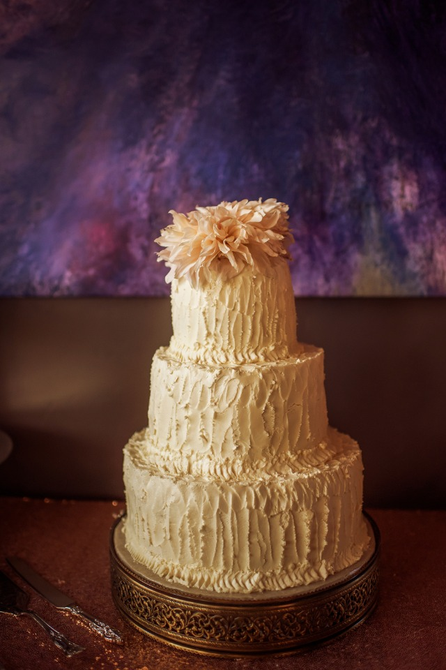 rustic frosted wedding cake with flower topper