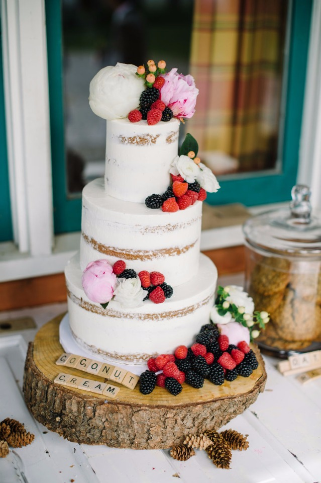 berry and flower topped nearly naked wedding cake