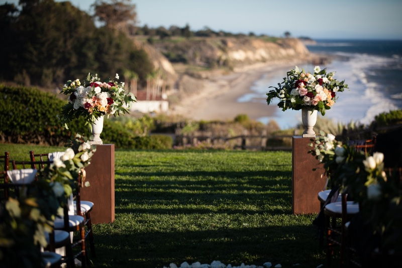 Ceremony Design and Planning by Magnolia Event Design & Planning on the Bacara Bluff overlooking the Pacific Ocean. Floral Design