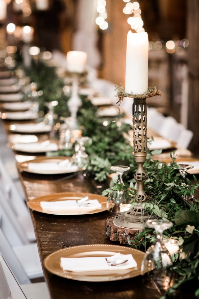 Greenery centerpiece with candles and gold chargers