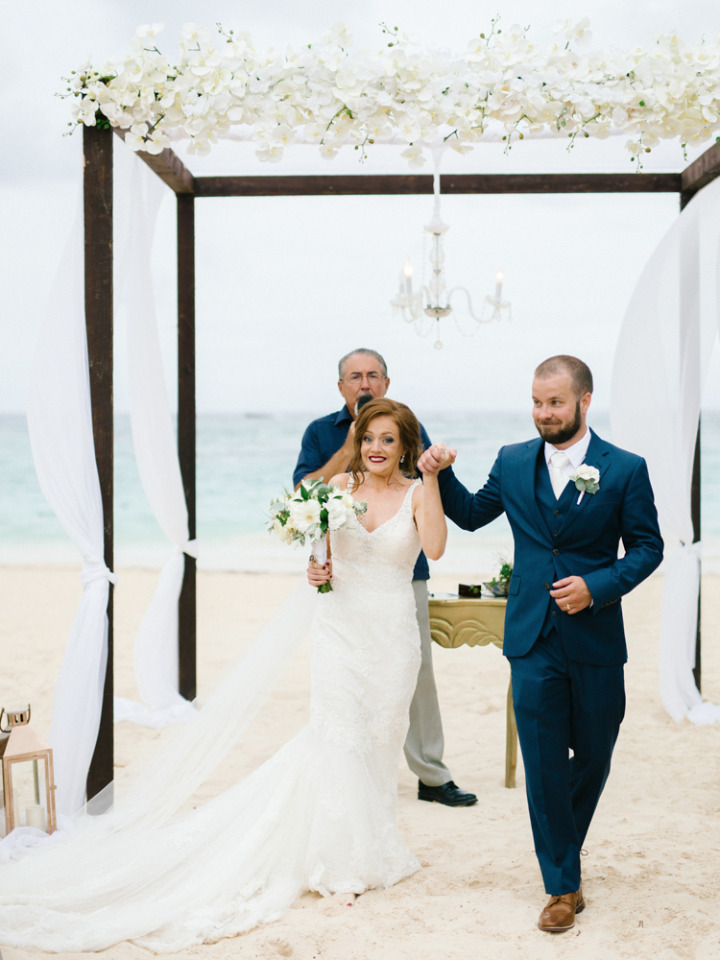 beautiful flower and chandelier beach ceremony arch