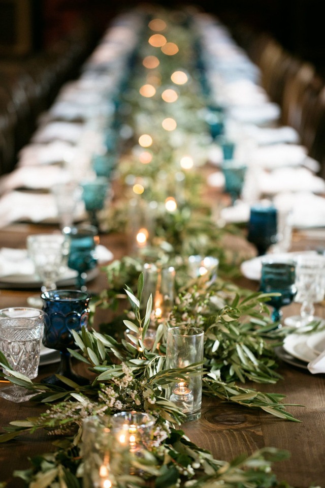 long family style wedding reception with greenry table runner