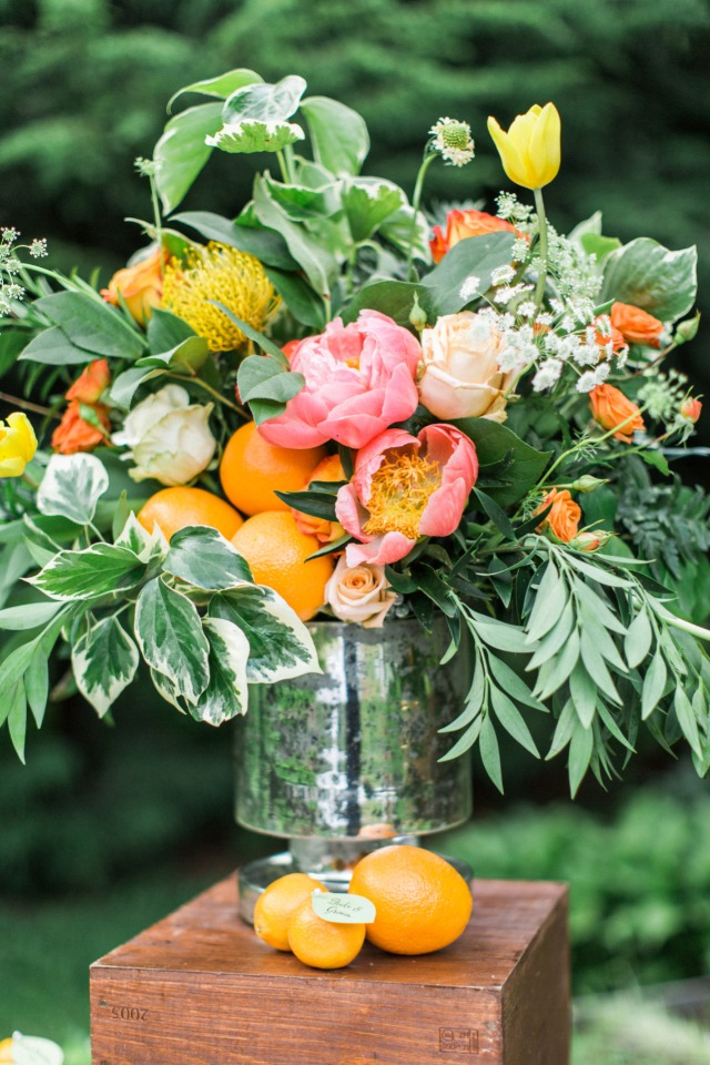 orange and pink flower and fruit arrangement