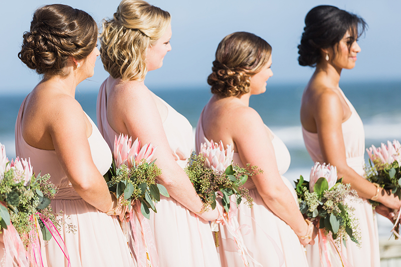 pink bridesmaids with king protea bouquets