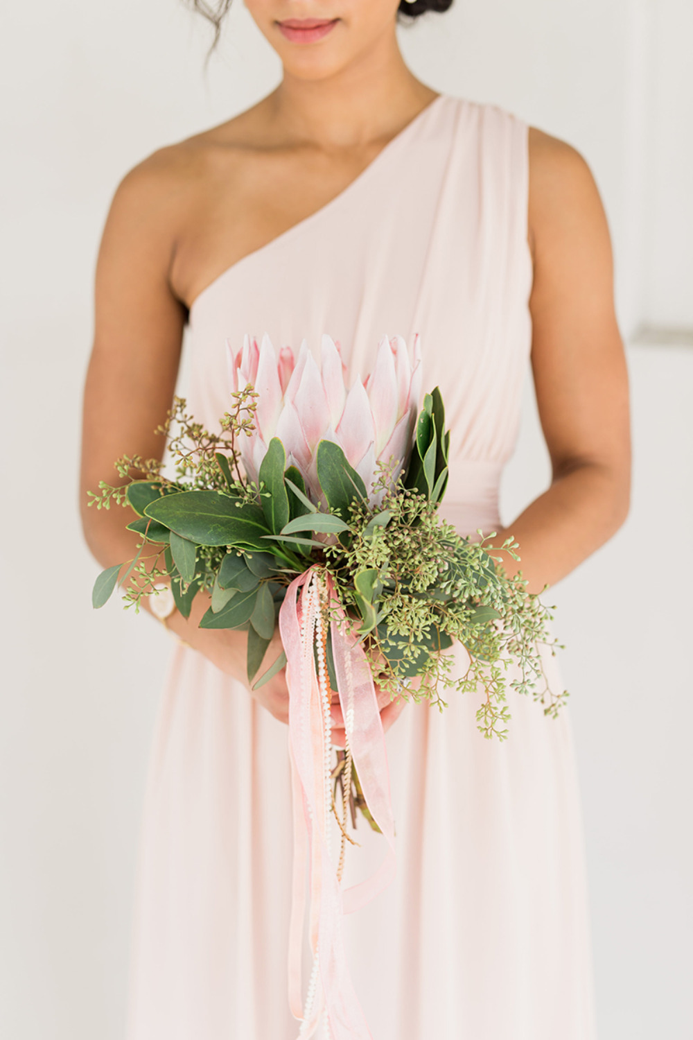 one shoulder blush bridesmaids dress with protea bouquet