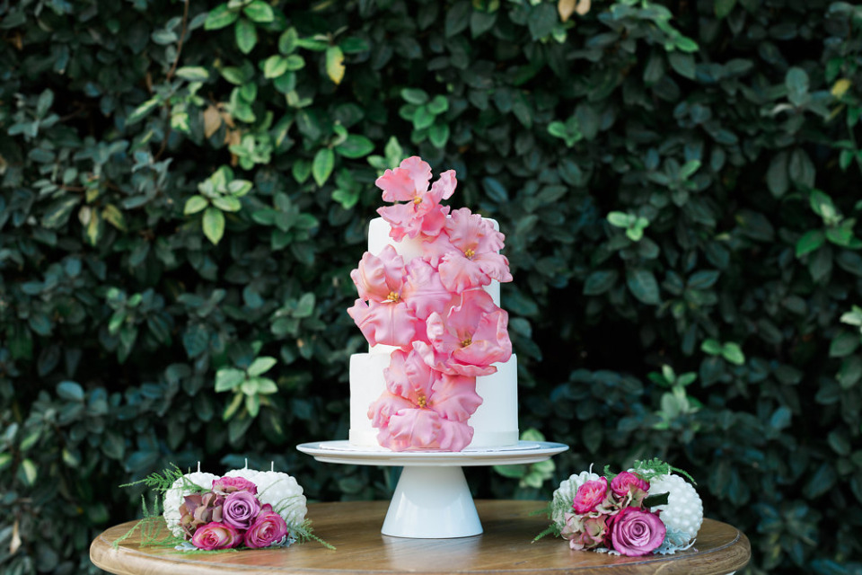 pretty white wedding cake with pink sugar flowers