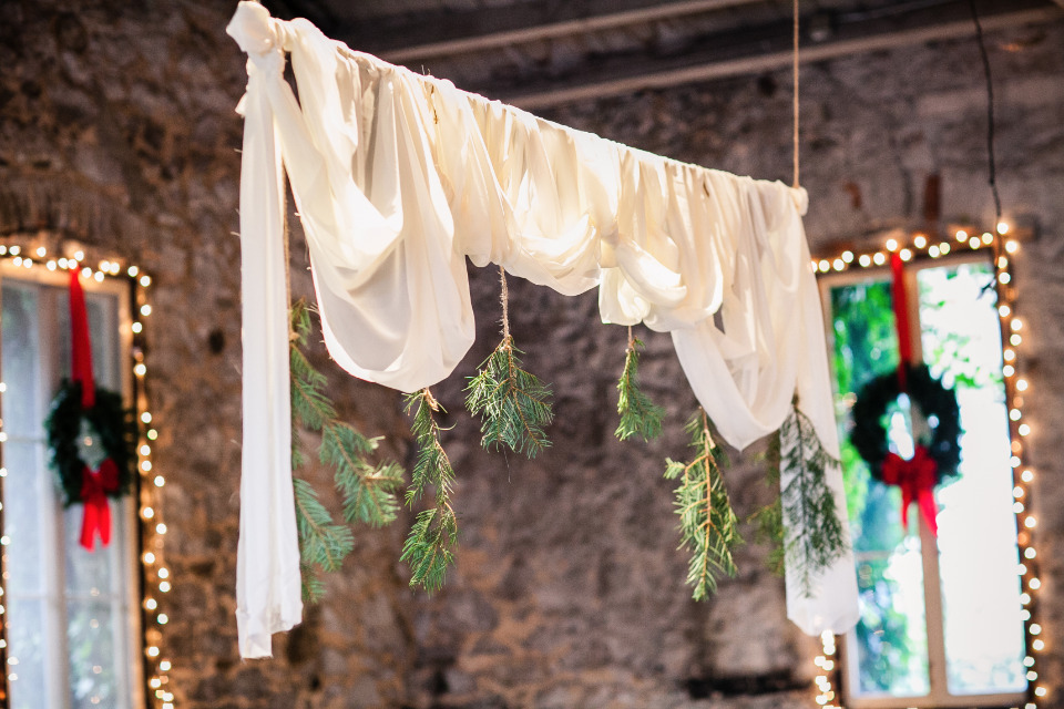 draped cloth and pine branch wedding ceremony backdrop