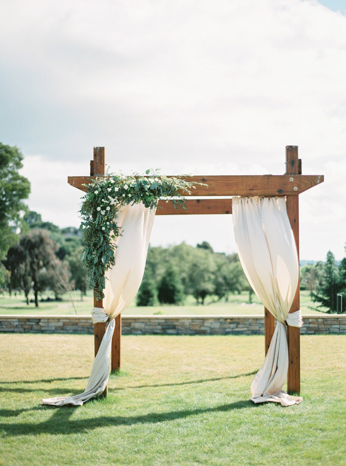 beautiful outdoor draped wedding ceremony arch