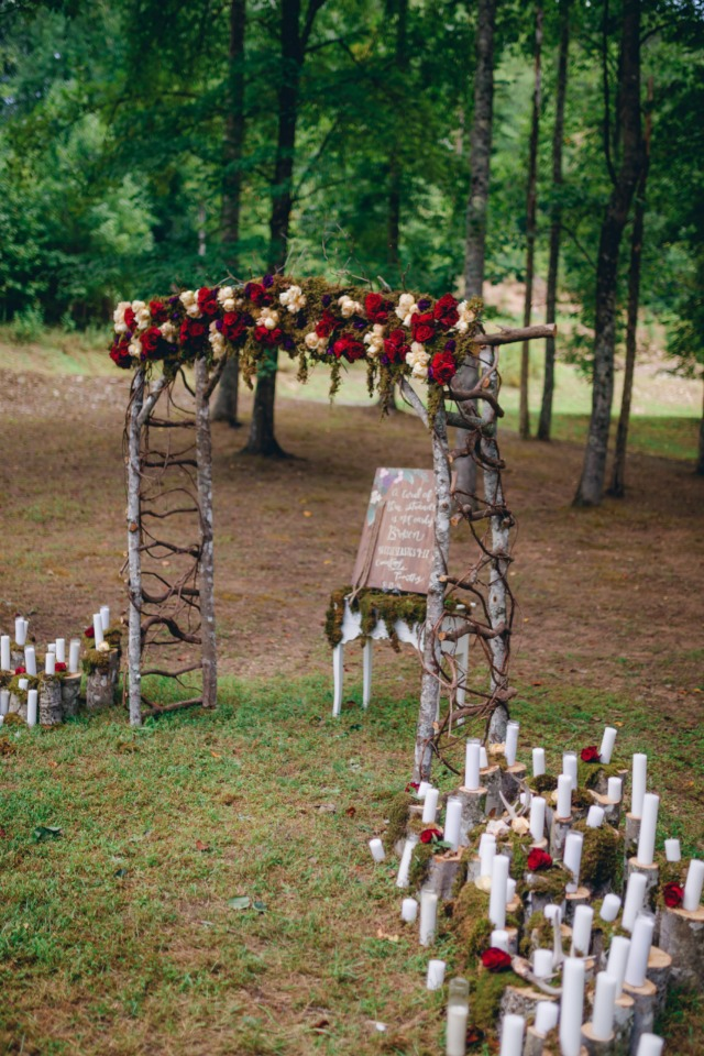 romantic floral wedding ceremony decor with hundreds of candles