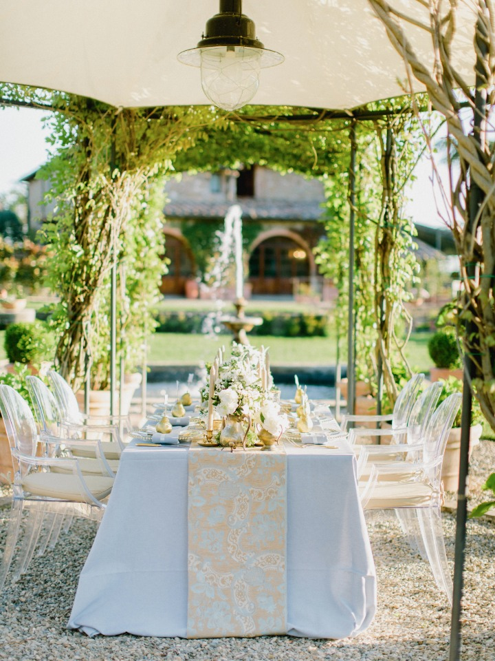 Beautiful garden reception with blue linens and gold details