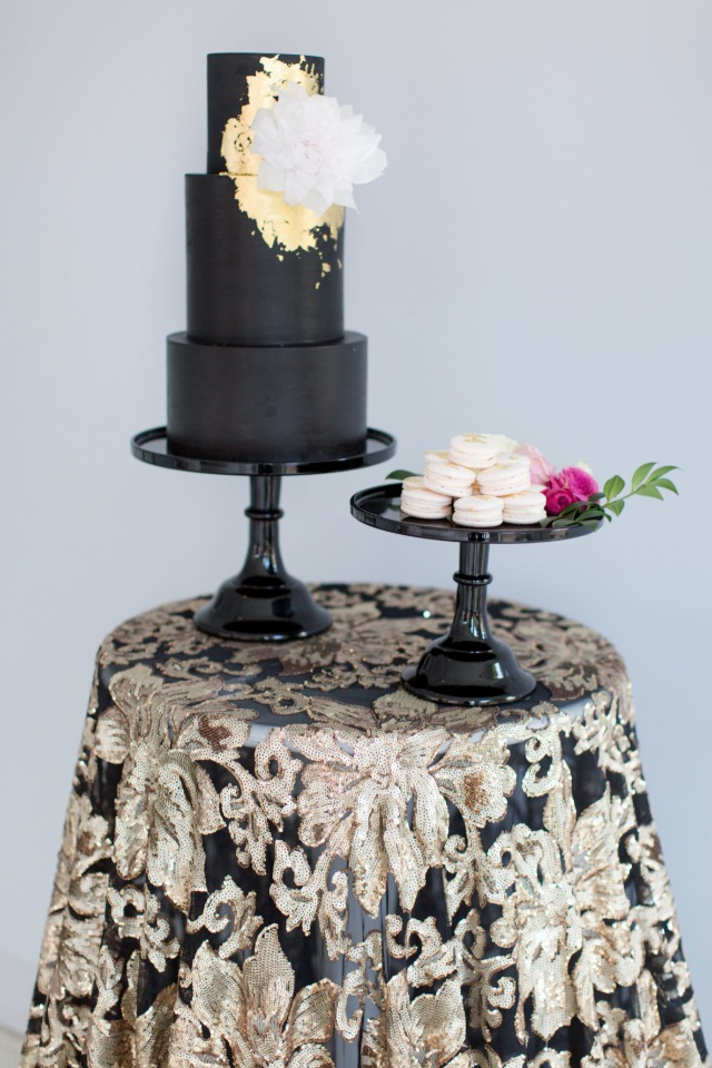 black and gold wedding cake with white macarons