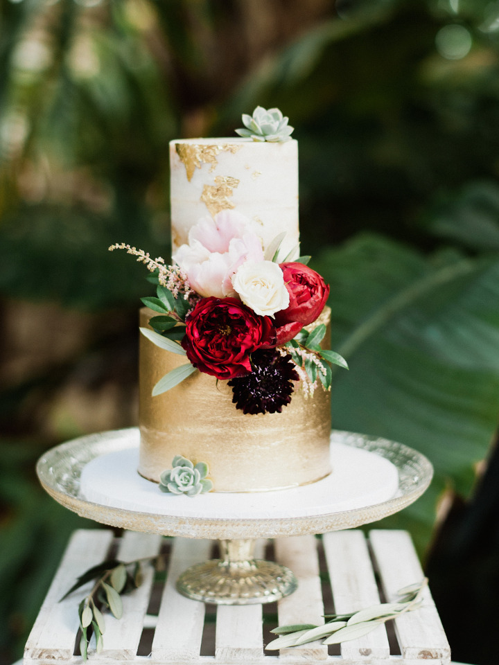 gold flaked wedding cake with flowers