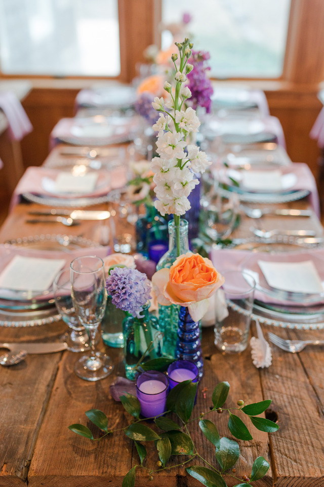 purple and teal wedding table decor with a beach vibe