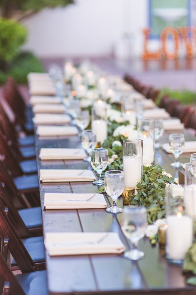 White candles and a garland centerpiece