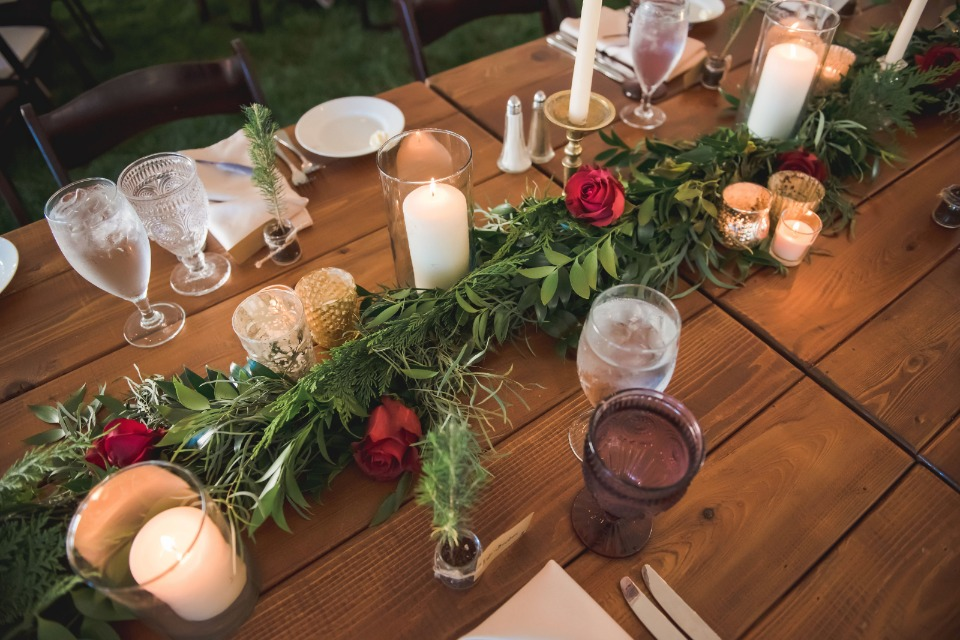 Garland centerpiece with red roses and candles