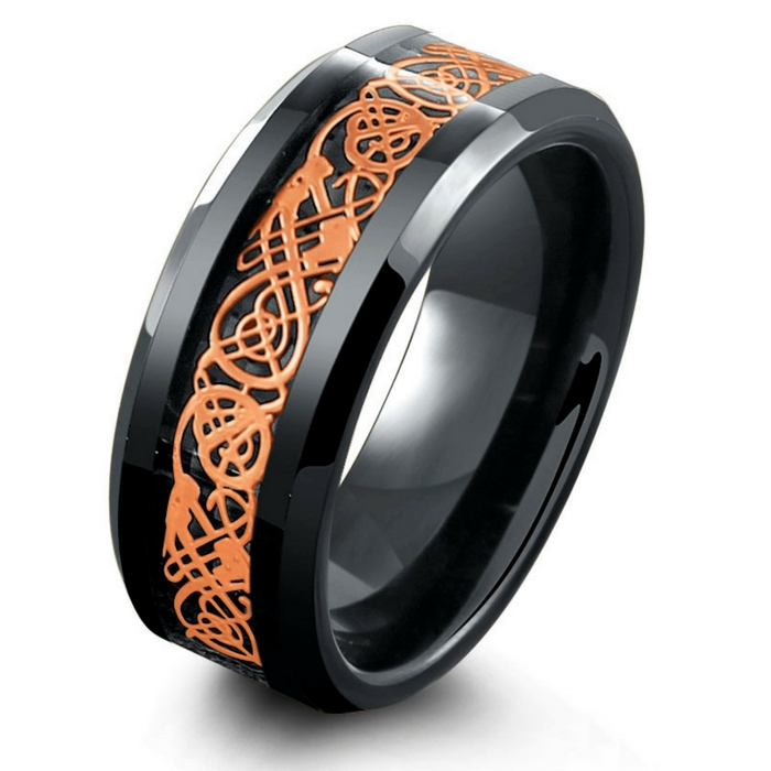 Mens black tungsten wedding ring with an 18k rose gold celtic inlay resting on top of a black woven carbon fiber inlay.