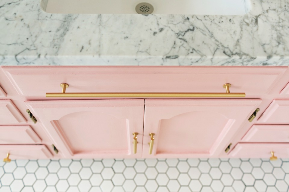 pink and gold bathroom cabinets topped with a little marble
