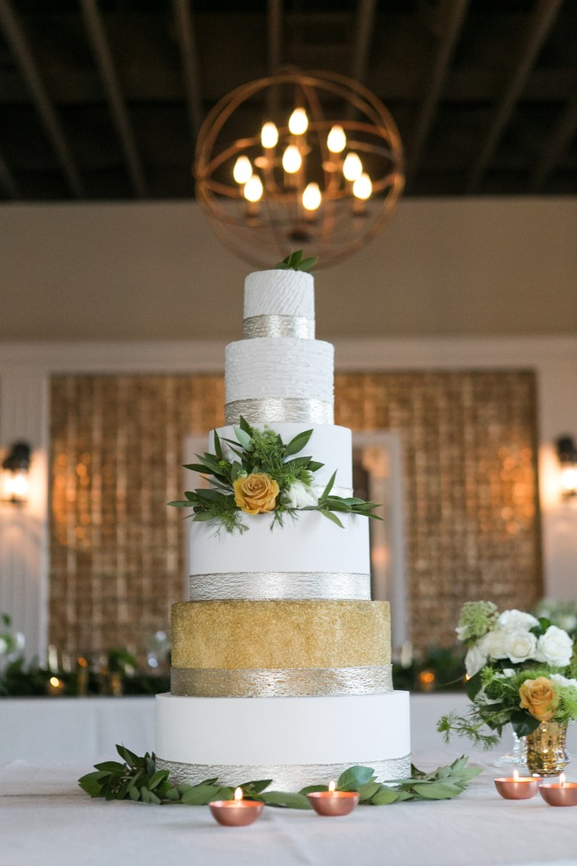 Gold silver and white cake with greenery