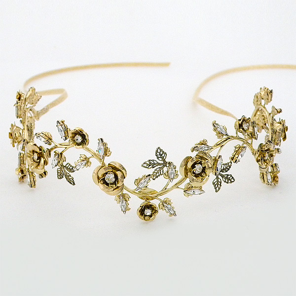 A swirling vine of shiny antique gold roses joined by crystal adorned leaves. Can be worn slightly up right as a crown, or can rest
