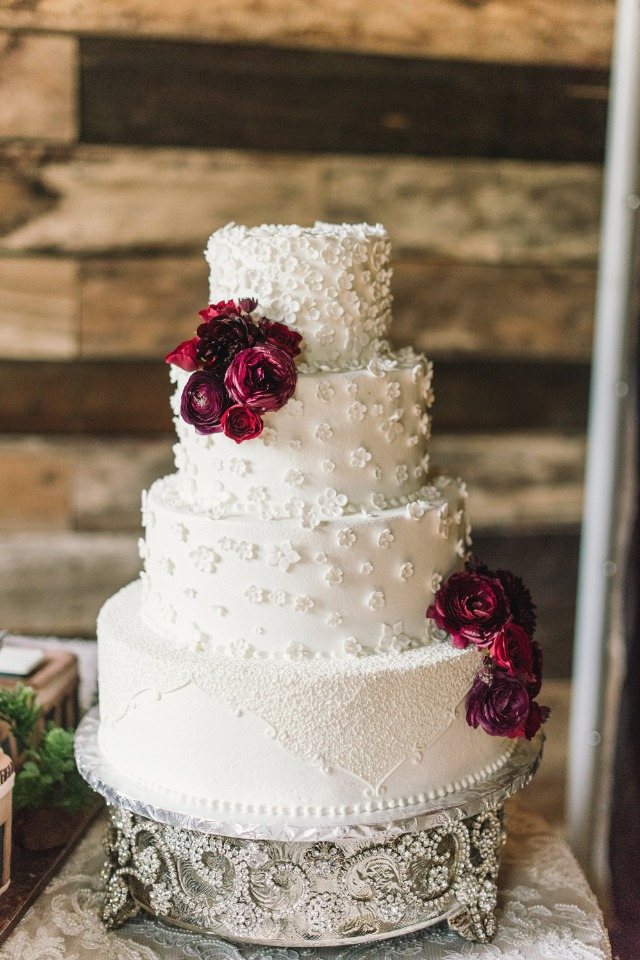 white cake topped with burgundy flowers