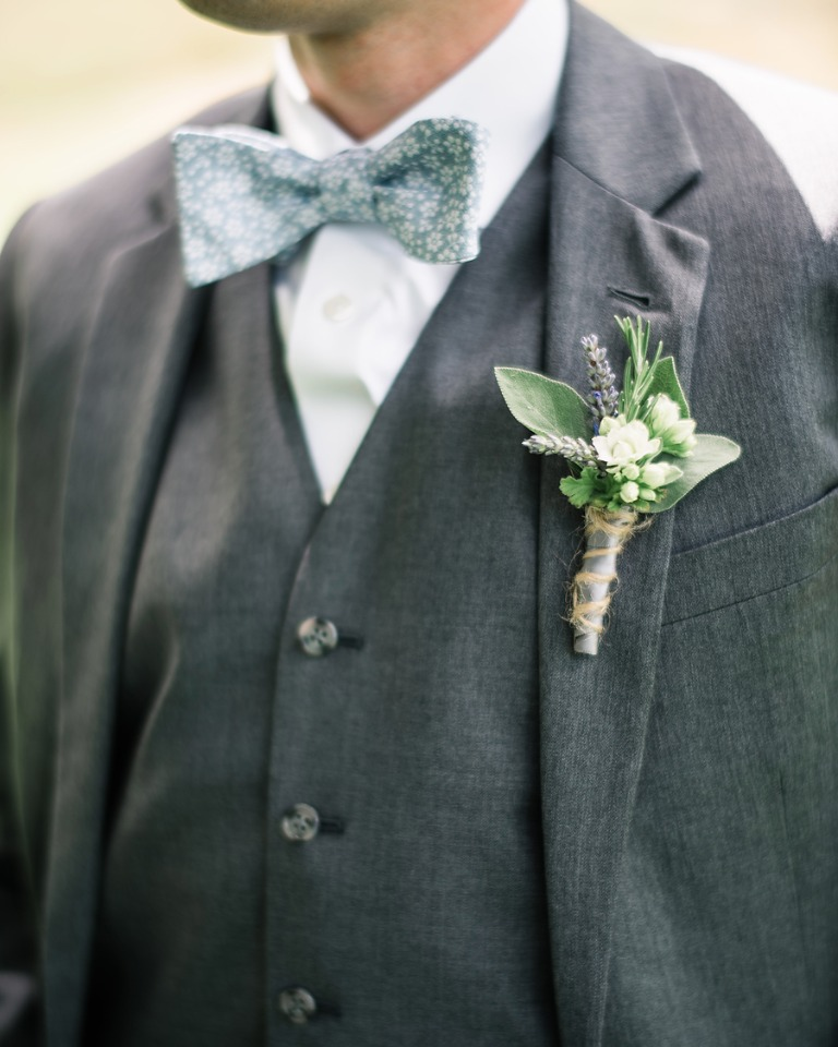 groom in grey suite and floral blue bow tie