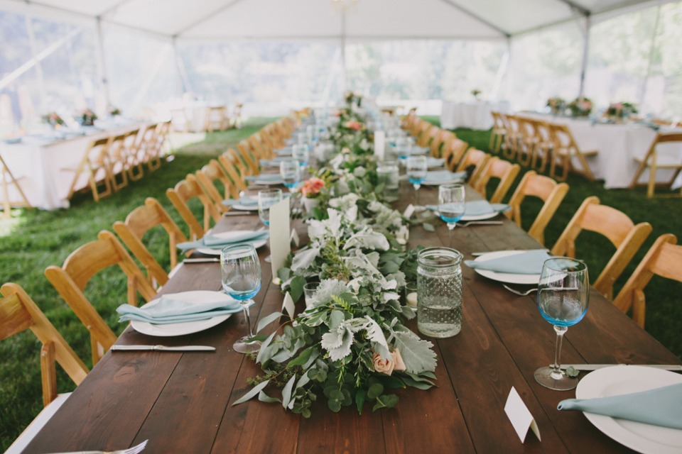 Green garland centerpiece on a wood table