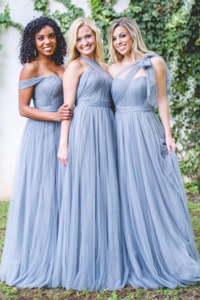 Girls in tulle dresses with blue flowy sashes.🎶 Rosalie Tulle Bridesmaid Dress from Revelry.